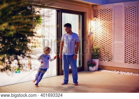 Happy Father And Son Having Fun Together, Playing Catch-ups At Home Patio At Night