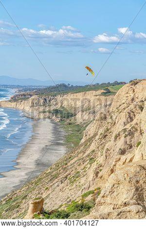 Rocky Mountain Bordering The Shoreline Of Ocean Aith Parachuters And Blue Sky