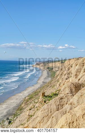 Scenic Nature Landscape Of Blue Ocean With Shoreline Bordered By Rocky Mountain