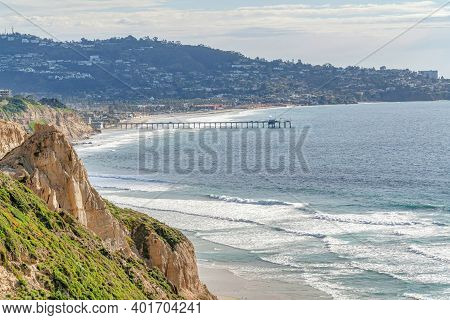 Pier On The Ocean With Shoreline Bordered By Mountain In San Diego California