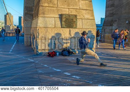 New York, Usa - March 9, 2020: Street Dancer Man Performs On The Brooklyn Bridge In Afternoon Light,