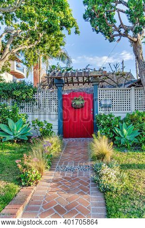 Red Wooden Gate With Pergola And White Fence Of Home With Pathway In The Garden