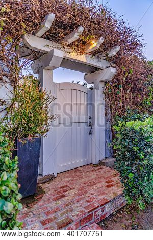 White Wooden Arched Gate With Pergola And Fence Covered With Overgrown Vines