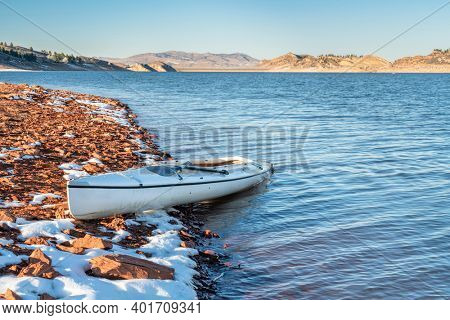 decked expedition canoe on a rocky shore of a mountain lake - Horsetooth Reservoir in northern Colorado in fall or winter scenery