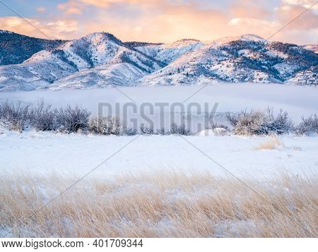 scenery of a mountain lake and valley covered by fog at winter sunrise - Horsetooth Reservoir at foothills of Rocky Mountains in Colorado