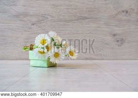 Bouquet Of Fresh White Marguerite Daisy Flowers And Small Gift Box Lying On Light Background. Spring