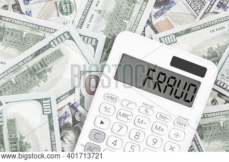 Fraud Text On A Calculator With Us Dollar Money On The Desk. Business And Finance Fraud Prevention O