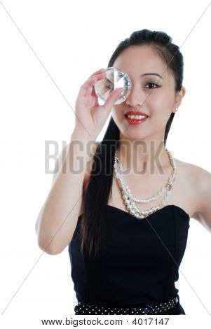 Oriental Woman Holding A Big Diamond To Her Eye