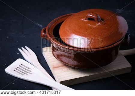 Earthenware Casserole With Wooden Cutlery And A Black Slate Base