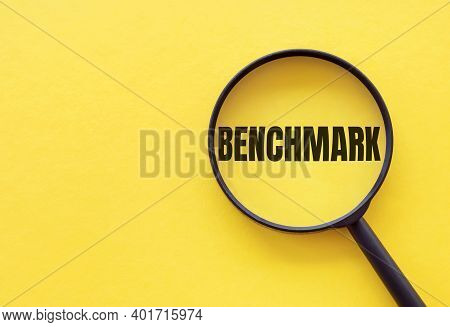 The Word Benchmark Is Written On A Magnifying Glass On A Yellow Background.