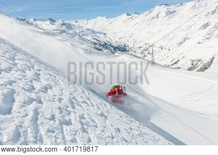Stock Picture Of A Freeride Skier That Is Skiing Fast Downhill In Deep Powder Snow. Big Mountains An