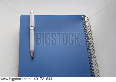 White Pen Attached To Blue Spiral Notebook On White Table. Selective Focus. Background Image With Co