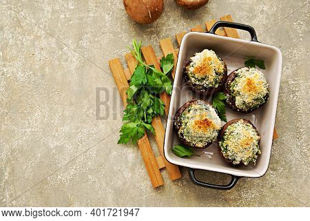 Baked Brown Mushrooms Stuffed With Spinach And Cheese, With Breadcrumbs And Cheese Crust In A Black