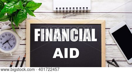 Financial Aid Written On A Black Background Near Pencils, A Smartphone, A White Notepad And A Green