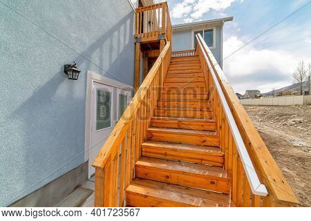 Close Up Of Wooden Stairway With Handrails At Home Exterior Against Cloudy Sky