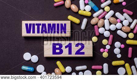 Vitamin B12 Is Written On Wooden Blocks Near Multi-colored Pills. Medical Concept