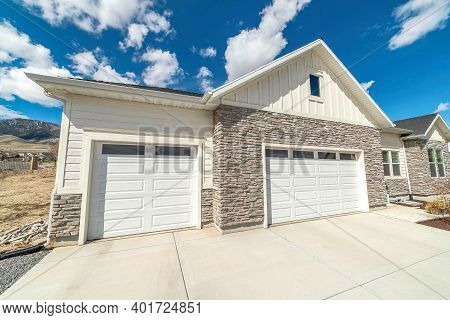 Facade Of Home With Gable Roof White Garage Doors And Stone Wall Against Sky