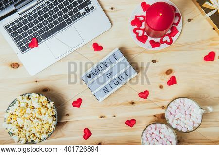 St. Valentines Day Movie Night Concept. Movie Night Message On Board, Laptop, Popcorn, Red Candle, G
