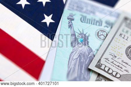 United States IRS Stimuls Check with Statue of Liberty Wearing Medical Face Mask Resting on American Flag.