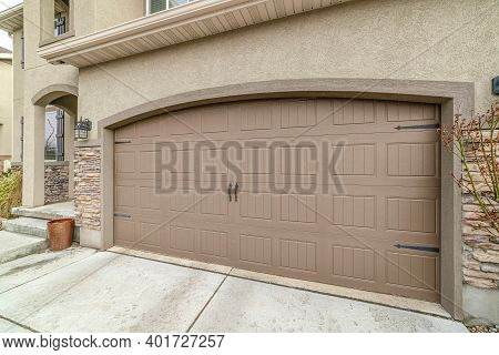Attached Garage Of House With Gray Hinged Paenelled Doors And Paved Driveway
