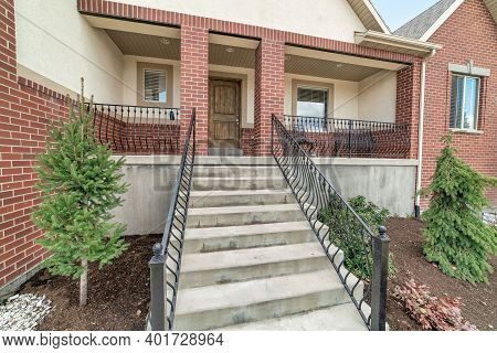 Porch And Concrete Stairs With Metal Handrails At Facade Of Red Brick House