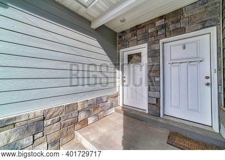 Side By Side White Wooden Front Doors Against Stone Wall At Townhouse Facade