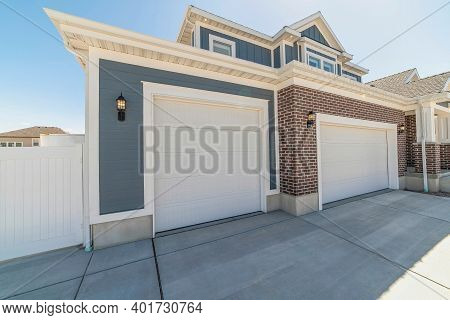 Front View Of Home Garage With Two White Doors And Brick And Wood Exterior Wall