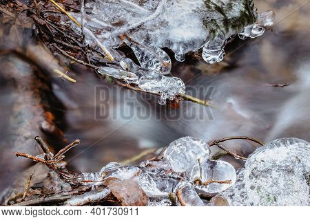 Clouse Up Of Icicles Near Wild Stream.snowy Winter Scenery.icicle In Nature Ice Background.cold Slip