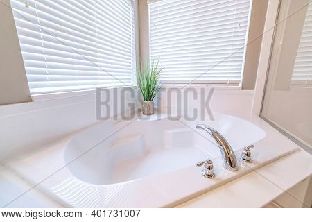 Built In Bathtub Inside A Bathroom With Indoor Plant And Two Windows With Blinds