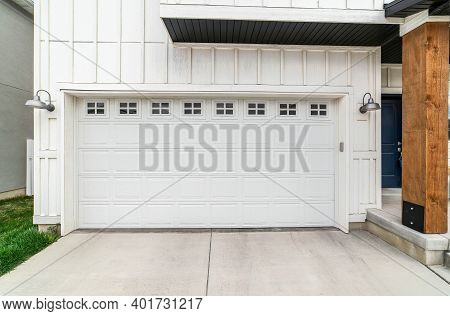 White Panelled Wooden Door Of The Attached Garage Of Home With Small Glass Panes