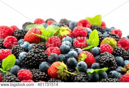 Berries. Various colorful berries background. Mint leaves, Strawberry, Raspberry, Blackberry, Blueberry close-up backdrop, isolated on white.