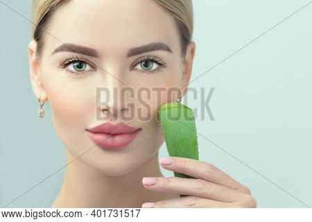 Skin care. Beauty Woman with perfect skin holding fresh leaf of Aloe Vera. Portrait of Beautiful Blonde Spa Girl with perfect healthy skin. Skincare, moisturizing. Proposing a skin care product.