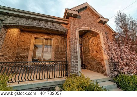 House Exterior View With Arched Entrance On The Gabled Porch With Brick Wall