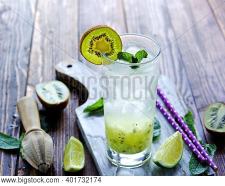 Soft Drink, Non-alcoholic Cocktail With Kiwi, Lime Juice, Sparkling Water And Ice In A Tall Glass On