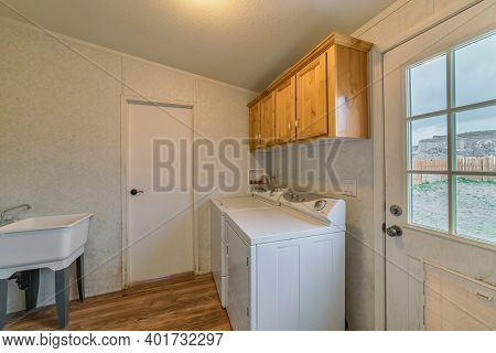 Laundry Room Of Home With Appliances And Glass Paned Door With View Of The Yard