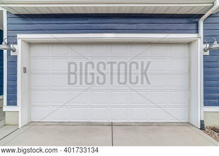 Wide White Wooden Garage Door Against Blue Exterior Wall Siding Of House