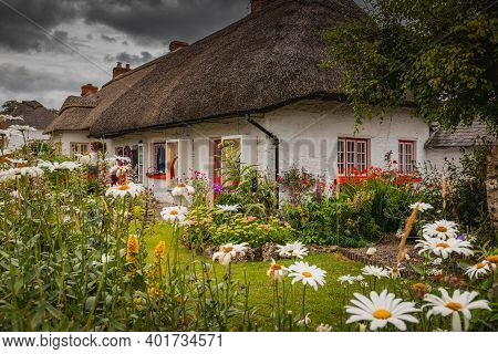 Adare, Ireland. Thatched Cottage In The Picturesque Village Of Adare, Co. Limerick Full Of Flowers I
