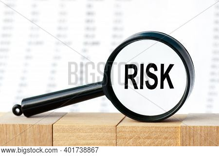 Looking Through A Magnifying Glass At The Word Risk, A Business Concept. Magnifying Glass On The Bac
