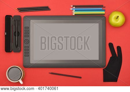 Graphic Monitor Stylus And Glove On Red Color Table. Black Tablet Computer With Blank Screen. High R