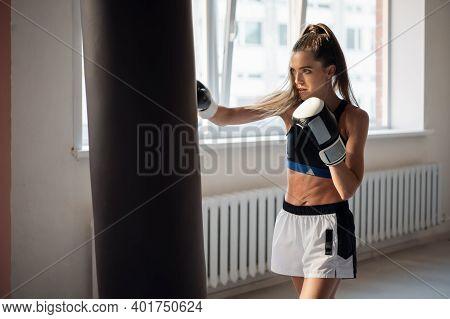 A Girl In Sports Clothes Is Engaged In Boxing And Works Out A Punch With Her Hand On A Punching Bag