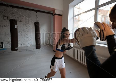 A Young Girl Conducts Kickboxing Training And Practices Paw Strikes With A Professional Boxer