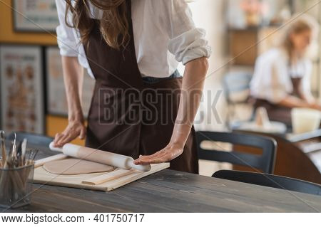 Young Woman On A Pottery Class Working With Rolling Pin. Artist Rolls Raw Clay Using Big Wooden Roll
