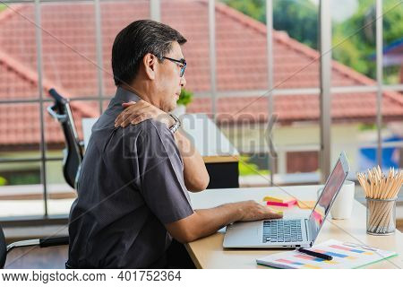 Asian Hard Senior Businessman Working With Laptop Computer Has A Problem With Shoulder Pain. Old Man