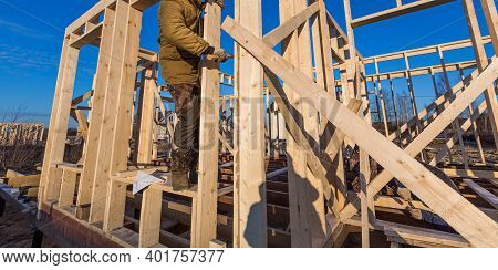 New Residential Construction Of Wooden Frame House And Worker. Roofing Construction. Wooden Construc