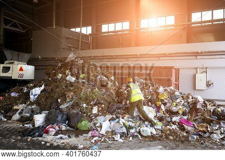 A Worker Sorts Through Garbage In A Factory For Waste Recycling.