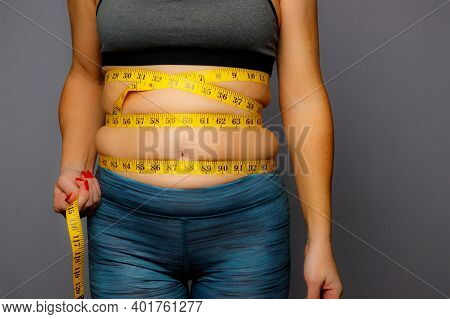 Woman In Active Wear With Squeezed Measuring Tape On A Gray Backgroundwoman In Active Wear With Sque