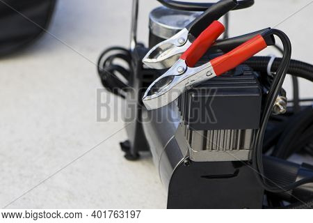 Pump Compressor For Inflating Car Wheels Close-up. Car Pump In A Black Case On A Gray Background. Th