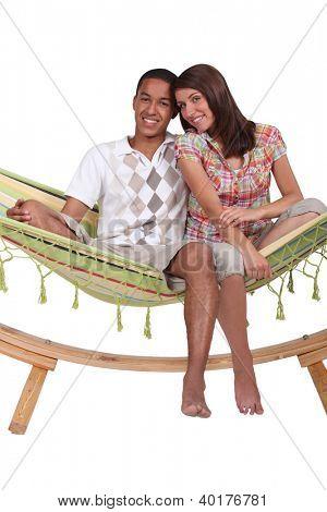 Happy couple sitting in a hammock