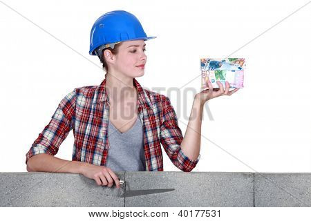 Woman holding a house made of money