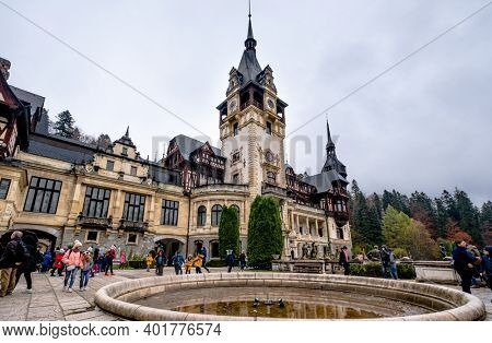 Sinaia, Romania - 30 November 2019: Tourists near inactive fountain in front of Peles Castle